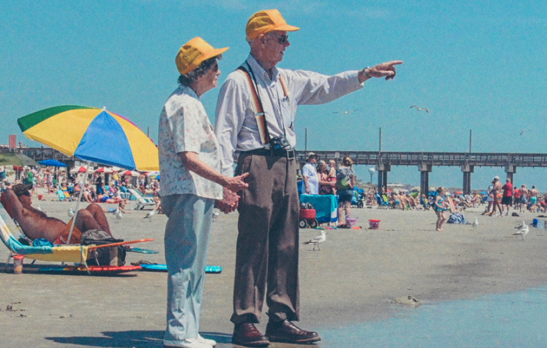 Elderly couple holding hands on a busy beach on a sunny day.