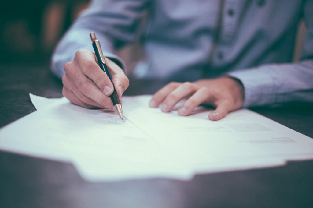 Closeup on a mans hands as he signs a piece of paper with a pen in his hand.
